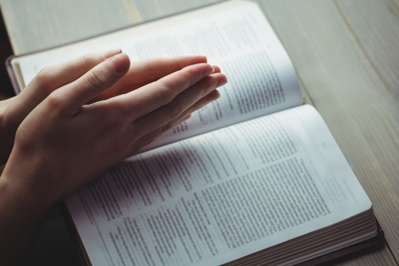 methodist: Woman praying with her bible on table