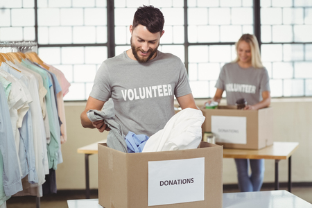 separating: Smiling man separating clothes from donation box in office and woman seen in background Stock Photo