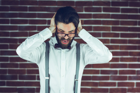 wall covering: Portrait of frustrated man covering ears against brick wall