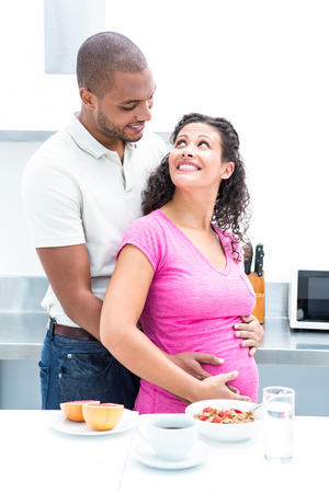 woman pregnant: Happy couple standing in kitchen while looking at each other at home