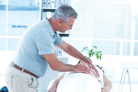 providing: Masseur providing massage to pregnant woman in spa Stock Photo