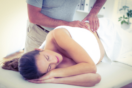 masaje: Sección media de masajista da masaje a la mujer durmiendo en la cama en spa