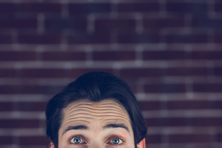 wrinkled brow: Portrait of man with raised eyebrows against brick wall