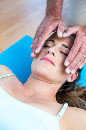 health club: High angle view of relaxed woman getting reiki treatment in health club