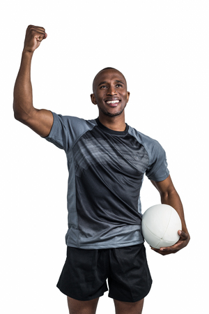 rugby ball: Happy sportsman with clenched fist holding rugby ball after victory standing over white background