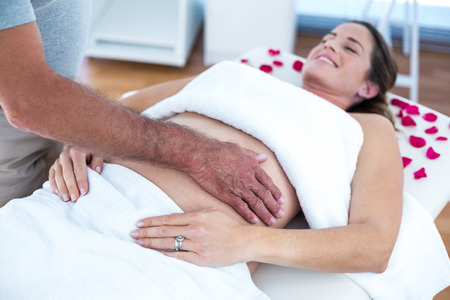 Receiving: Pregnant woman lying on bed receiving massage in spa Stock Photo