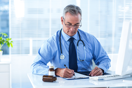 Male doctor writing prescription white sitting at desk in hospital