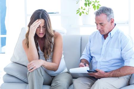 psychiatrist: Psychiatrist advising to depressed pregnant woman while sitting on sofa