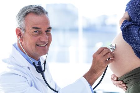 homme enceinte: Portrait de médecin de sexe masculin utilisant stéthoscope examen femme enceinte dans la clinique