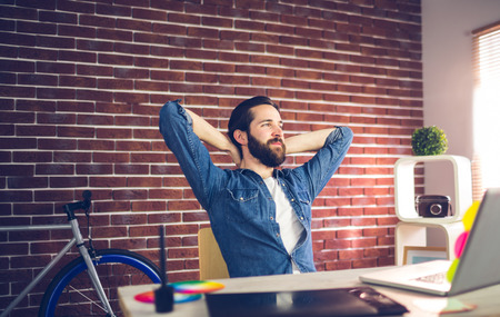 hands behind back: Thoughtful businessman with hands behind back relaxing in creative office