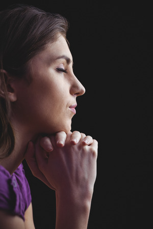 brethren: Woman praying with hands together on black background Stock Photo