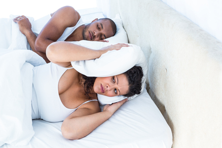 bed time: Stressed wife sleeping besides snoring husband at home