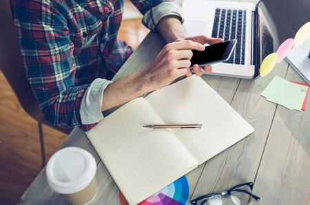 Buik van creatieve redacteur behulp van mobiele telefoon en laptop op kantoor