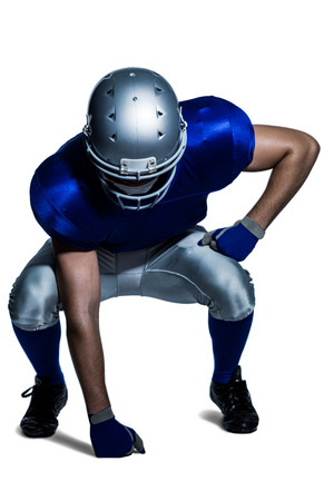 knee bend: American football player in uniform bending against white background Stock Photo