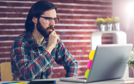 casual business man: Confident businessman using laptop on desk in creative office