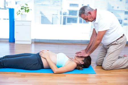 reiki: Therapist performing reiki on young pregnant woman