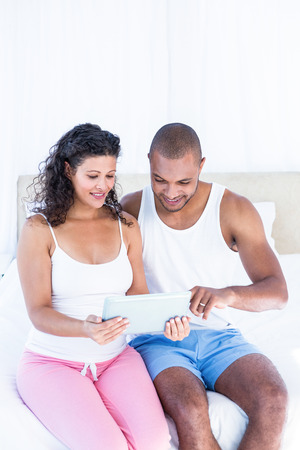 pregnant woman with husband: Husband with pregnant wife holding digital tablet while sitting on bed at home