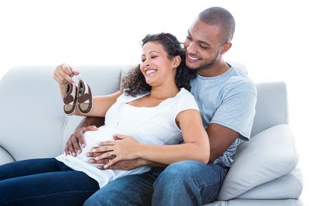 homme enceinte: Enthousiaste jeune couple avec des chaussures de bébé assis sur le canapé à la maison Banque d'images