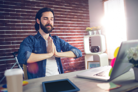clasped hand: Businessman with hand clasped doing yoga in creative office