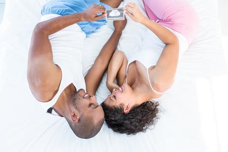 sonogram: Feliz marido y mujer sosteniendo sonograma mientras se relaja en la cama