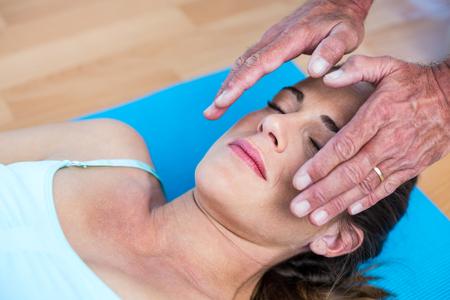 reiki: Relaxed woman getting reiki treatment in health club Stock Photo