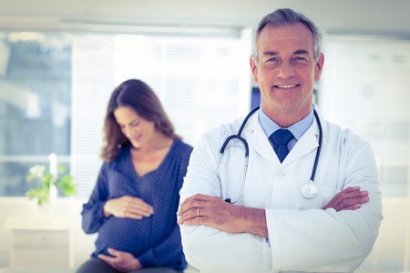 gynaecologist: Portrait of confident male doctor with pregnant woman in background at clinic