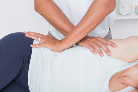 fisioterapia: Doctor que examina a la pelvis del paciente en el consultorio médico