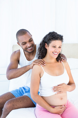 husband: Husband massaging pregnant wife shoulders on bed at home