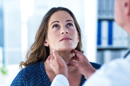 mid adult women: Woman looking up while getting examined by doctor in clinic Stock Photo