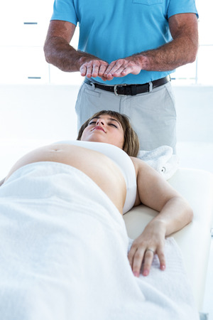 reiki: High angle view of pregnant woman relaxing while male therapist performing reiki at health club Stock Photo