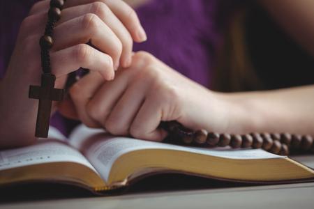 różaniec: Kobieta, modląc się z jej Biblii na stole