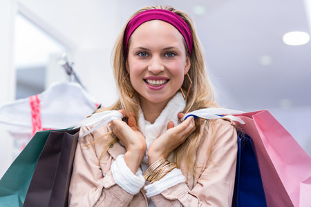 clothing store: Portrait of smiling woman with shopping bags in clothing store Stock Photo