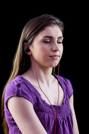 eyes looking down: Woman listening to music with eyes closed on black background
