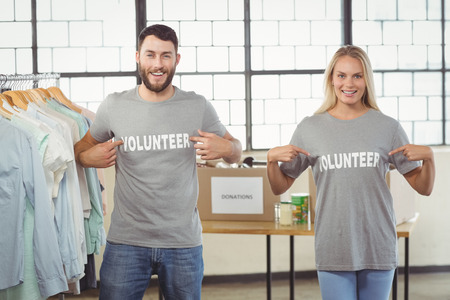 volunteer point: Portrait of man and woman showing volunteer text on tshirts while standing in office