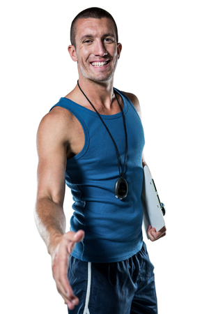 Portrait of happy personal trainer giving handshake against white background