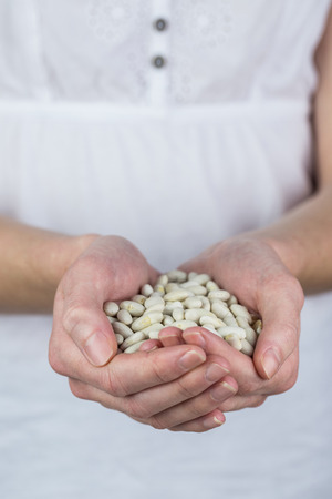 lima bean: Woman showing handful of lima beans in close up
