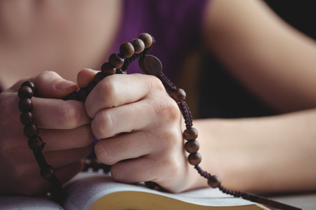 jehovah: Woman praying with her bible and rosary beads in close up