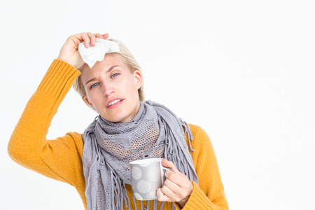 cold background: Close up of woman feeling her forehead and drinking from a cup