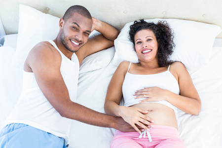 pregnant woman with husband: Portrait of pregnant wife with husband lying on bed at home Stock Photo