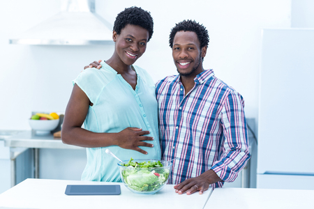 pregnant woman with husband: Portrait of happy cheerful couple standing in kitchen