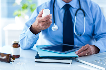 doctor holding pills: Cropped image of male doctor with prescription medicine bottle in clinic Stock Photo