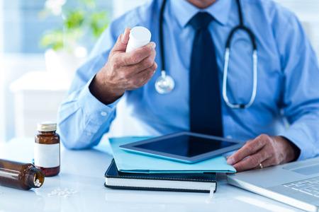 medicina: Imagen recortada de médico hombre con botella de medicina con receta en la clínica Foto de archivo