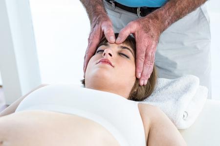 reiki: Calm woman receiving reiki treatment from male therapist Stock Photo