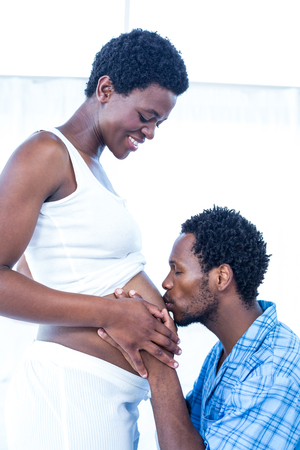 kissing pregnant belly: Affectionate husband kissing belly of his pregnant wife at home