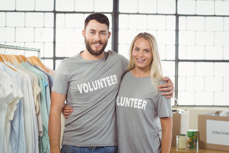 arms around: Portrait of joyful volunteers with arms around standing in creative office