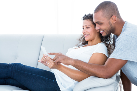 sonography: Happy couple looking at sonography relaxing on sofa at home Stock Photo