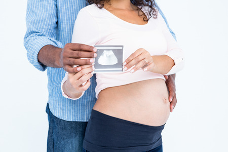 sonogram: Midsection of couple holding sonogram against white background Stock Photo