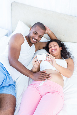 young wife: Pregnant wife holding smartphone with husband lying on bed at home
