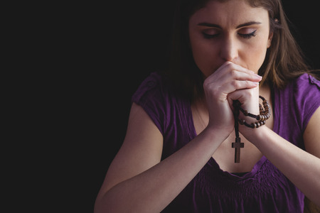 Woman praying with wooden rosary beads  on black background