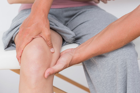 knee: Doctor examining his patient knee in medical offic Stock Photo